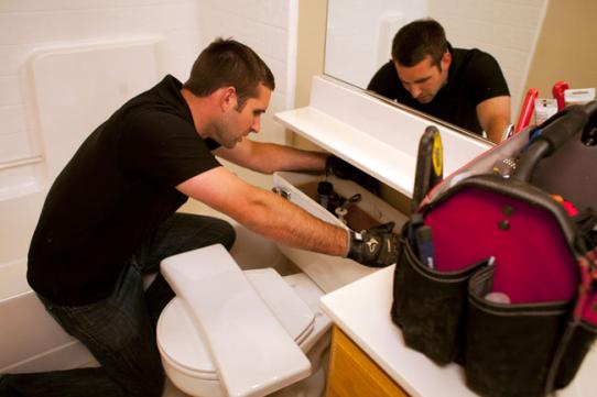 Plumber in Bakersfield repairs a toilet by replacing the float valve